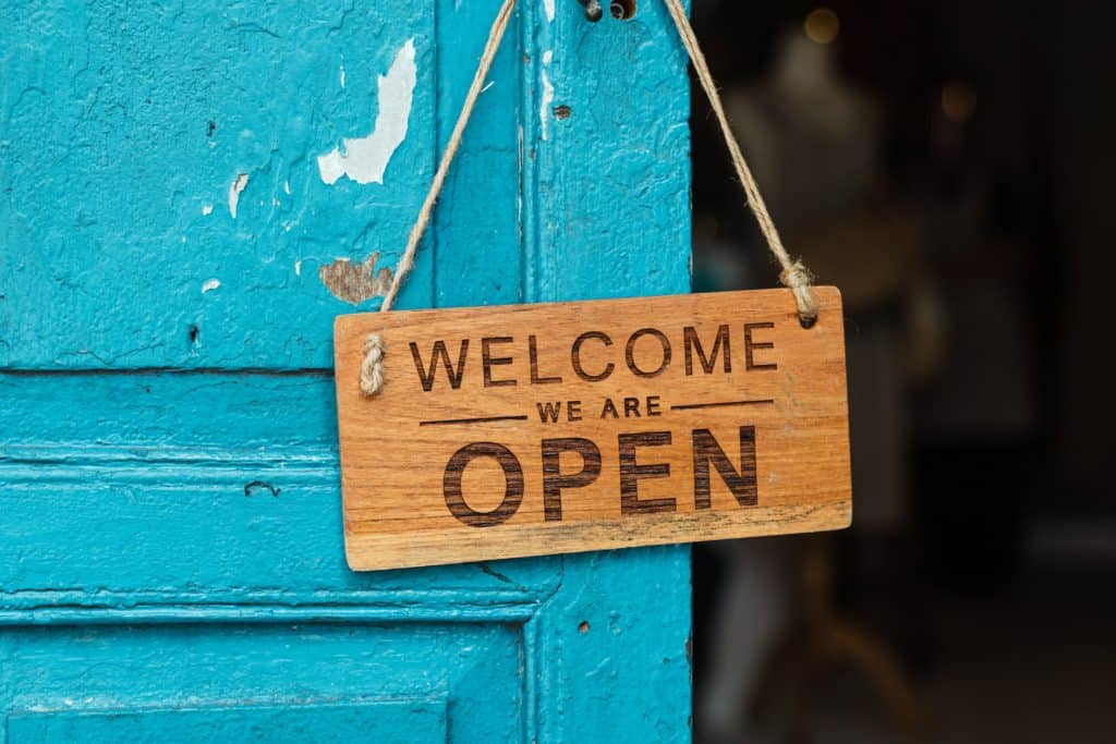 """Wood sign hanging off of a door knob that says """"welcome, we are open"""""""